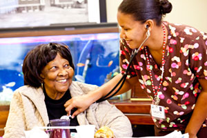 A Riverside PACE nursing assistant listens to the heartbeat of a PACE participant at the Center in Hampton